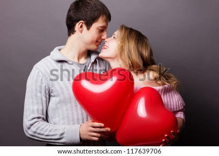 Young happy couple with red balloon