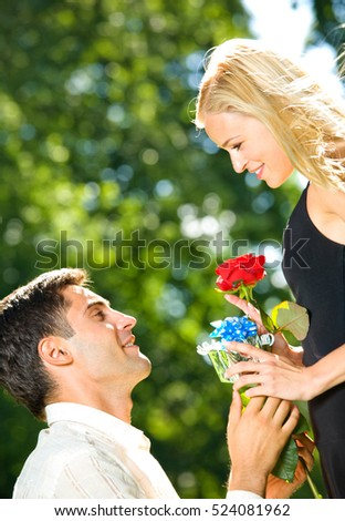 Young happy couple with rose and gift, outdoors. Love, flirt, romantic, relations, celebration theme concept.