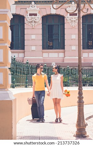 Young happy couple with suitcases walking along the street - stock photo