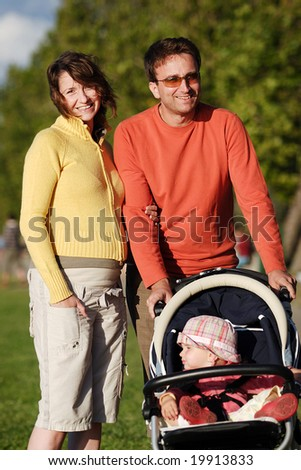 Young happy couple with their child walk in autumn