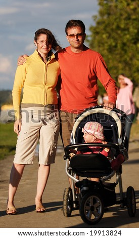 Young happy couple with their child walk in autumn, the man embrace the woman - stock photo