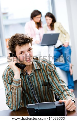 Young happy customer service worker receiving phone calls at office, smiling. - stock photo