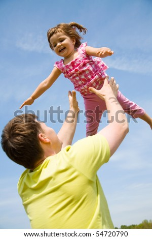 young happy dad playfully tosses his little daughter in the sky in the sky - stock photo