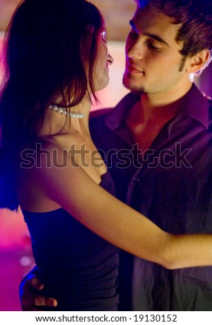 Young happy dancing amorous couple at celebration - stock photo