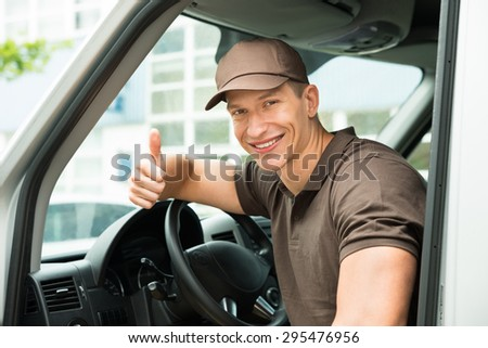 Young Happy Deliverymen Showing Thumb Up Sign In Van