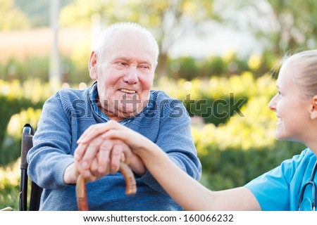 Young happy doctor giving support to his elderly patient. - stock photo