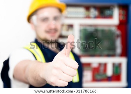 Young happy electrician showing thumbs up after finishing his job. Selective focus on the hand. - stock photo