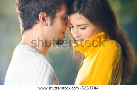 Young happy embracing couple walking together outdoors - stock photo