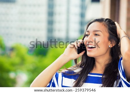 Young happy excited laughing woman talking on mobile phone isolated outdoors city urban background.  - stock photo