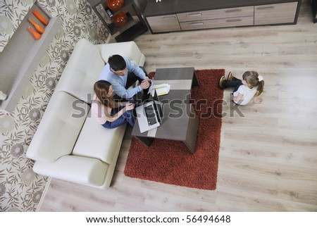 young happy family at bright and modern living room puting money in piggy bank and working on laptop computer on home finance - stock photo