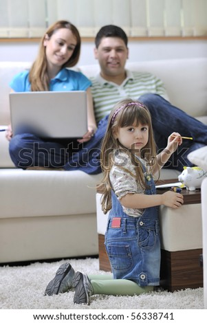 young happy family at bright and modern living room putting money in piggy bank and working on laptop computer on home finance