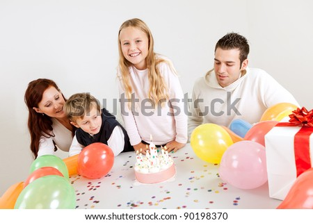 Young happy family celebrating birthday at home - stock photo