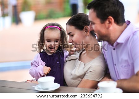 Young happy family enjoying cup of coffee In cafe together