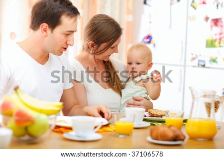 Young happy family having breakfast together - stock photo