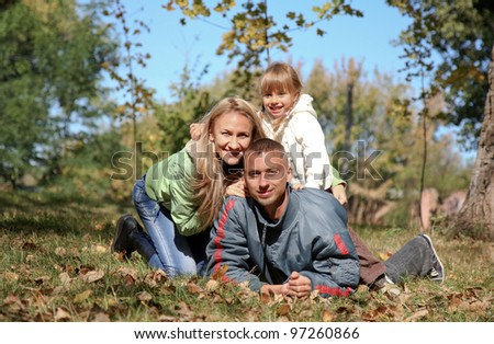 Young happy family in autumn park.