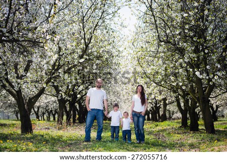 Young happy family in cherry blossom spring garden - stock photo