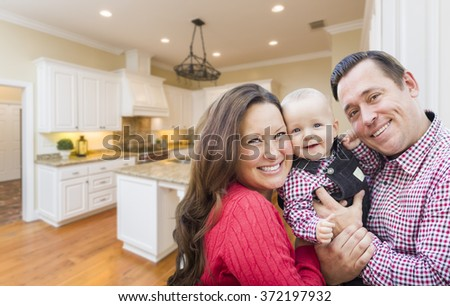 Young Happy Family Inside Beautiful Custom Kitchen. - stock photo