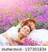 Young happy family laying down on fresh lavender meadow, hugging outdoors, summer season, romance and love concept - stock photo