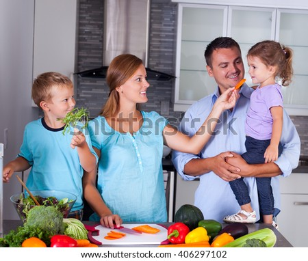 Young happy family making dinner together in the kitchen. Mother, father and two children.