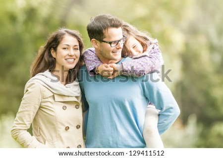 Young happy family of three having fun together outdoor. Pretty little daughter on her father back. Parents and girl look happy and smile. Happiness and harmony in family life. Family fun outside. - stock photo