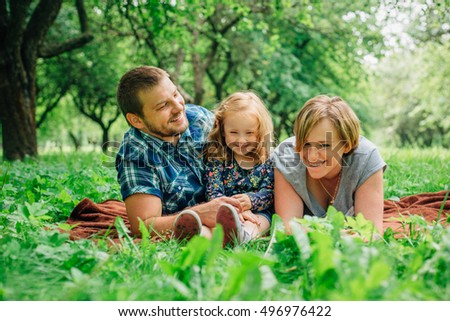 Young happy family of three lying on blanket in the park having fun. Happy parenting concept