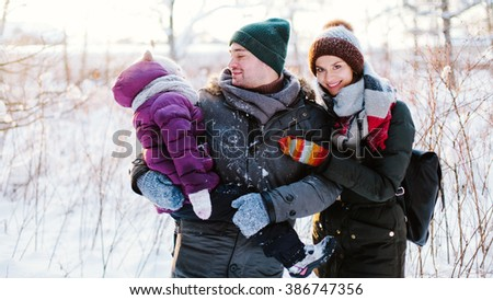 Young happy family of three people walking in the winter forest and enjoying life. Portrait of a beautiful family in the winter forest - stock photo