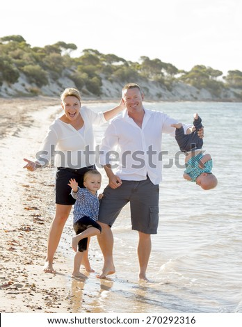 young happy family playing on sand together at beach sea shore enjoying summer holidays , father holding baby boy upside down, mother and cute little daughter having fun in vacation concept - stock photo