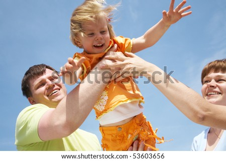Young happy family playing with daughter outdoors background on the blue sky