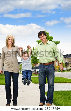Young happy family playing with son on sidewalk - stock photo