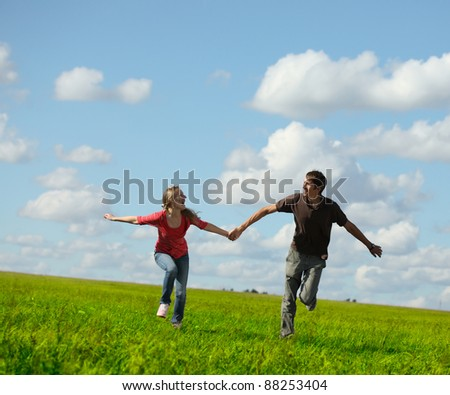 Young happy family running on a green meadow - stock photo
