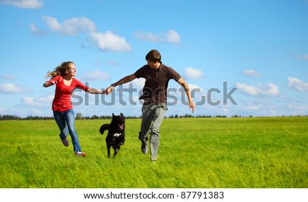 Young happy family running with dog on a green meadow - stock photo