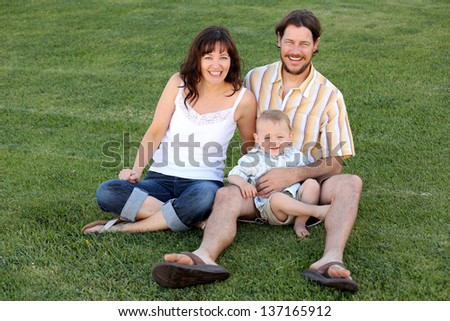 Young happy family sitting in green grass