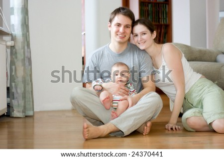 young happy family sitting on floor in their apartment - stock photo