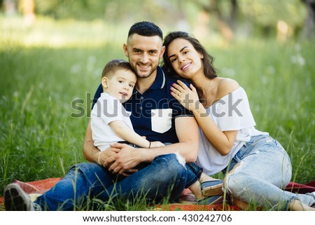 Young happy family spending their time in park  on picnic