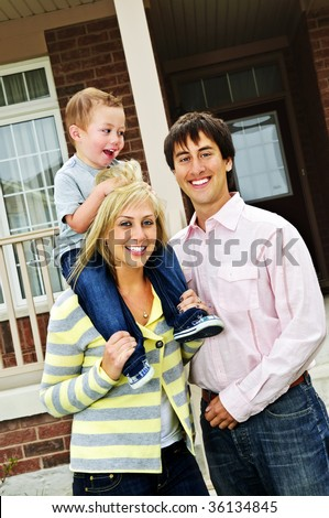 Young happy family standing in front of new home - stock photo