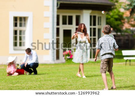 Young happy family - the children and the parents playing on the meadow - stock photo