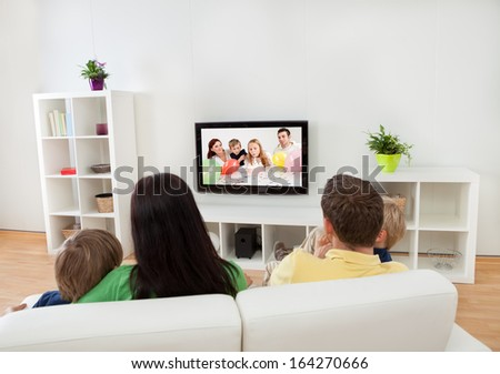 Young happy family watching TV at home - stock photo