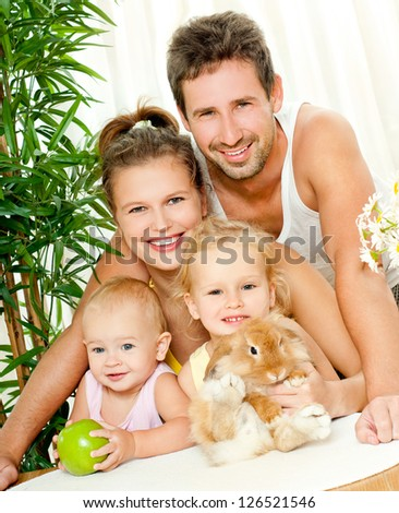 Young happy family with a pet rabbit - stock photo