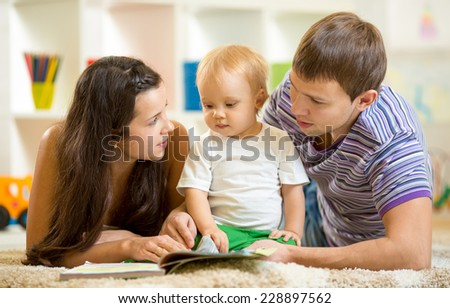 Young happy family with baby son read children book laying on floor