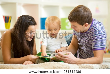 Young happy family with kid boy reading children book - stock photo