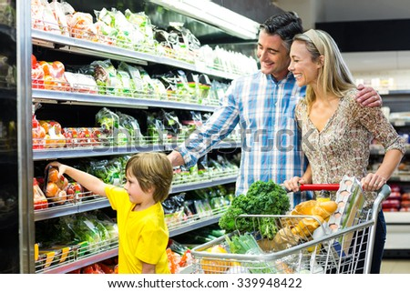 Young happy family with their son at supermarket - stock photo
