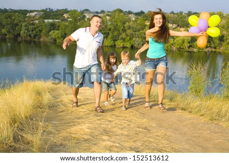 Young happy family with two children in the village - stock photo