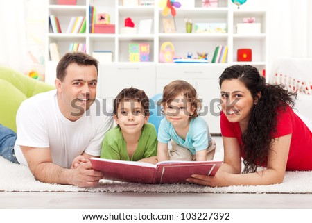 Young happy family with two kids reading a story book - laying on the floor - stock photo