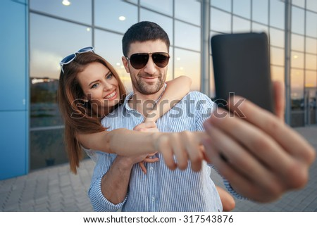 Young happy fashion couple in casual clothing with dark sunglasses taking photo of themselves with a smart phone near the glass windows of the shop or cafe, summertime vacation - stock photo