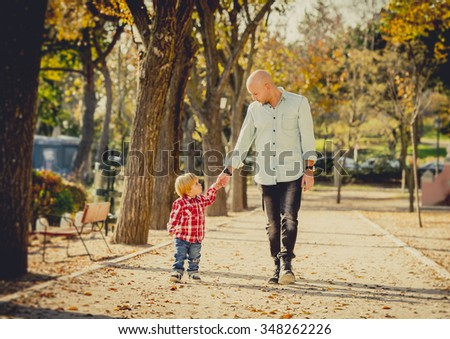 young happy father and his beautiful little 2 years old son walking together on Autumn park with trees having fun playing and sharing a sunny day in family love and childhood concept