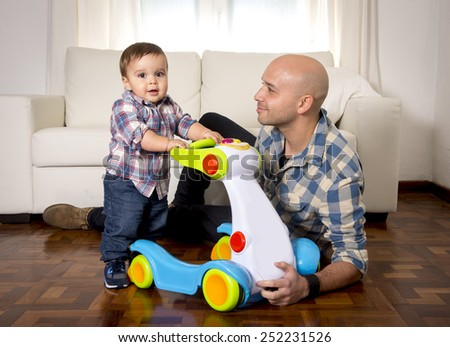 young happy father and little one year old son walking with baby walker taking his first brave steps at home in living room excited and playful in childhood and growth concept - stock photo