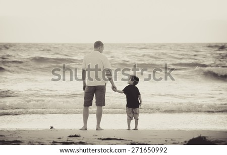young happy father holding hand of little son walking together on the beach with barefoot in sand in front of sea waves, the kid smiling and having fun  with dad in Summer sunset coast - stock photo