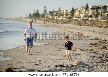 young happy father walking and little son running and playing on the beach with barefoot in sand in front of sea waves, the kid smiling and having fun together with dad in Summer vacation concept  - stock photo