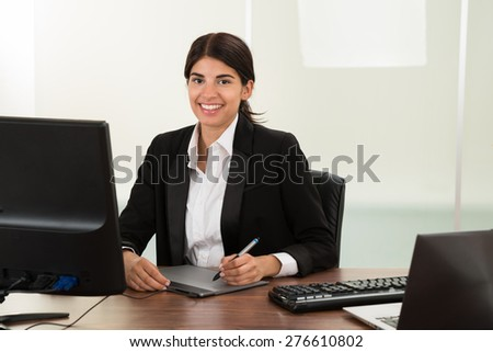 Young Happy Female Designer With Graphic Tablet Sitting At Desk