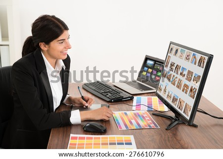 Young Happy Female Graphic Designer In Office. Photographer owns copyright for images on screen - stock photo